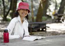 Woman reading outdoors. Woman sitting at a picnic table in the outdoors reading a book Stock Photo