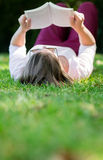 Woman reading outdoors Stock Images
