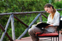 Woman reading outdoors Stock Photo