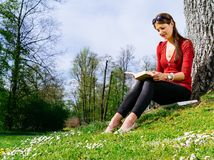 Woman reading outside in spring Stock Image
