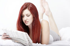Woman reading a paper on her bed Stock Photo