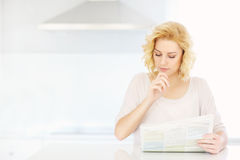 Woman reading paper in the morning Royalty Free Stock Image