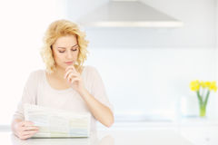 Woman reading paper in the morning Stock Photo