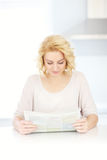 Woman reading paper in the morning Stock Images