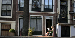 Woman reading paper outside. Woman sitting outside in the sun to read a newspaper Royalty Free Stock Photos