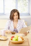 Woman reading papers at breakfast Stock Photos