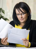 Woman reading paperwork. Portrait of middle aged woman wearing spectacles reading paperwork Stock Photos