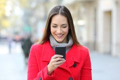 Woman reading a phone message in winter. Front view portrait of a happy woman reading a phone message in winter in the street royalty free stock image