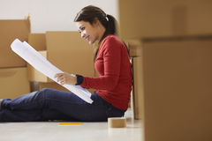 Woman reading plans of new house during move Royalty Free Stock Photography