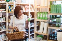 Woman reading product information on label. Woman choosing products in ecological shop with healthy food and reading product information on label Royalty Free Stock Images