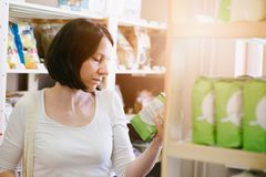 Woman reading product information on label. Woman choosing products in ecological shop with healthy food and reading product information on label Stock Photo