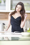 Woman reading recipe book Stock Images