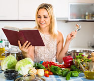 Woman reading recipe book in kitchen Stock Photos
