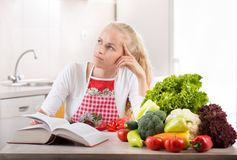 Woman reading recipe book. Pretty young blonde woman reading recipe book and preparing vegetables for lunch. Bright kitchen in background Stock Photography