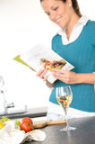 Woman reading recipe cooking book kitchen salad Royalty Free Stock Image