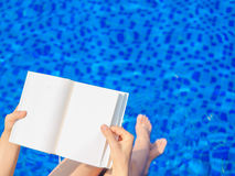 Woman reading and relaxing. Near luxury swimming pool Royalty Free Stock Photos