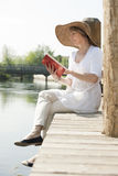 Woman reading by the river. Woman realxing while reading a book by river Stock Photography