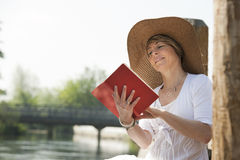 Woman reading by the river. Woman realxing while reading a book by river Stock Image