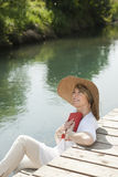 Woman reading by the river. Woman realxing while reading a book by river Royalty Free Stock Photography