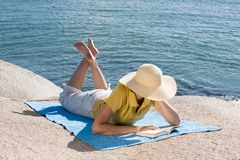 Woman reading at the sea Stock Photo