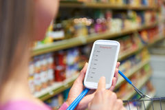 Woman Reading Shopping List From Mobile Phone In Supermarket Royalty Free Stock Photography