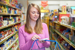 Woman Reading Shopping List From Smartphone In Supermarket. Woman Reads Shopping List From Smartphone In Supermarket stock image
