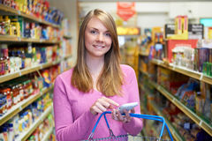 Woman Reading Shopping List From Smartphone In Supermarkey. Woman Reads Shopping List From Smartphone In Supermarkey stock photo