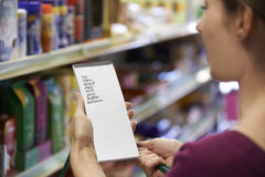 Woman Reading Shopping List In Supermarket. Close Up Of Woman Reading Shopping List In Supermarket stock image