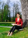 Woman reading and sitting against a tree Stock Photo
