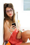 Woman reading on smartphone in her room Royalty Free Stock Image
