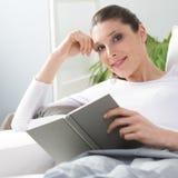 Woman reading on sofa Stock Photos