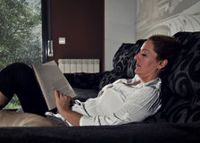 Woman reading on the sofa quietly Stock Photography