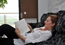 Woman reading on the sofa quietly Stock Photos