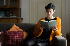 Woman Reading on a Sofa. Woman with Short Hair Reading a Book on a Sofa royalty free stock photo