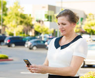 Woman reading something on smart phone stock photography