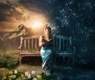 Woman reading in sun or rain. A woman is quietly reading in both sun and rain royalty free stock photo