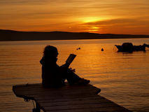 Woman reading in the sunset. A silhouette of a young woman sitting in the dock by the sea holding a open book in their hands (read the book) in a beautiful Royalty Free Stock Image