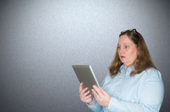 Woman reading a surprise on your tablet Stock Images