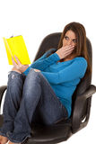 Woman reading surprised in chair Stock Image