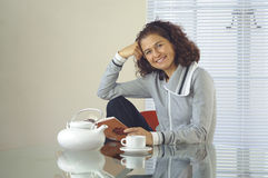Woman reading at a table. Female sitting at a table with a pot of tea and a book while smiling at the camera Royalty Free Stock Images
