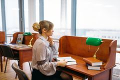 Woman reading at the table in university library. Pretty young woman reading book at the table in university library. Female person in knowledge depository royalty free stock image
