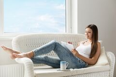 Free Woman Reading Tablet At Home Lying Down At Sofa Next Window. Morning Coffee Break. Beautiful Happy Girl Resting With Digital Touch Stock Photos - 216769603