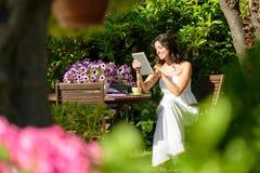 Woman reading on tablet in garden. Happy woman reading on tablet pc in garden on summer morning while breakfast. Woman enjoying communication technology on Royalty Free Stock Image
