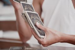 Woman is reading Tarot cards in cafe stock images