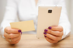 Woman reading telephone number from business card and calling cu Royalty Free Stock Photo
