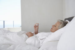 Woman Reading Temperature From Thermometer. Middle aged woman reading temperature from thermometer in bed Stock Photography