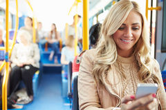 Woman Reading Text Message On Bus. Sitting On Chair Smiling With Passengers In Background stock photography