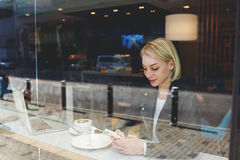 Woman is reading text message on cell phone, while is sitting with net-book in coffee shop Royalty Free Stock Image