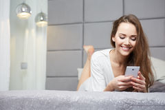 Woman reading a text message in her bright bedroom Stock Photography