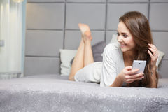 Woman reading a text message in her bright bedroom Stock Image